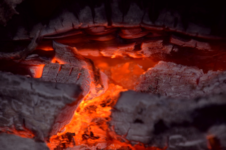 abstract burning firewood close up view, red glowing pieces of firewood in a indoor fireplace abstract macro shot