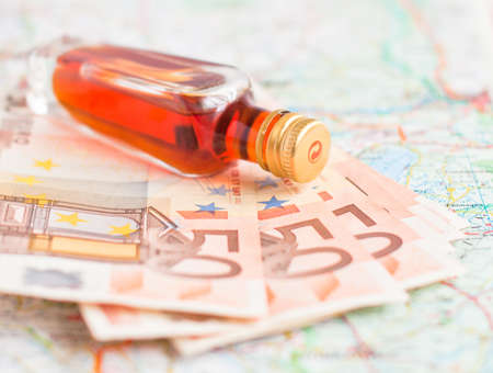 Bottle of alcohol and money on a road map photo