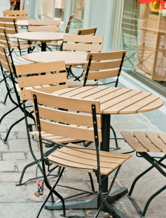 Tables and chairs of a restaurant outside early morning Stock Photo
