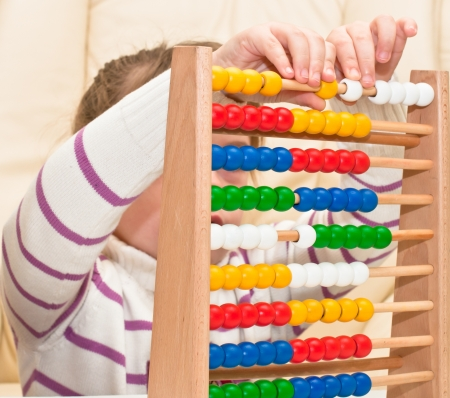 Little Girl contemplates the basics of arithmetic on his abacus  photo