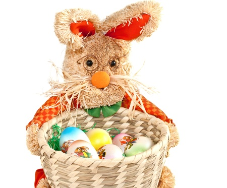 basket of easter eggs and toy rabbit on white background  photo