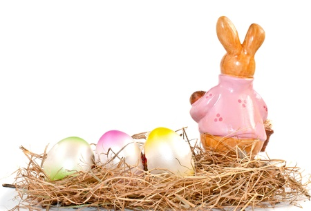 Colorful easter eggs and rabbit on straw