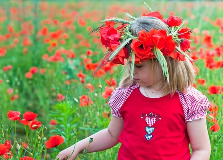 Little girl in a wreath from poppies