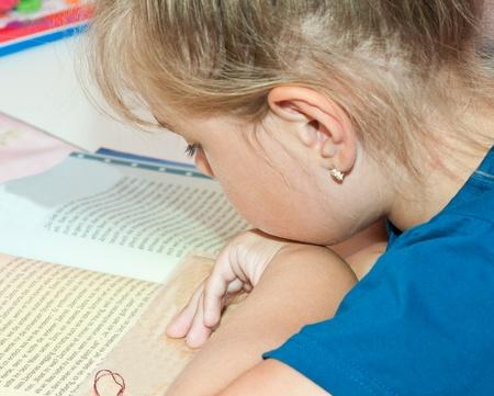 Brunette little girl reading a book  Stock Photo