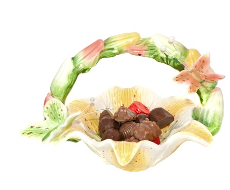 Assorted chocolate candies ,chocolate, in a ceramic vase close-up on white background