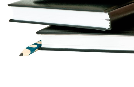 Two diary stacked lying next to a  pencil on a white background