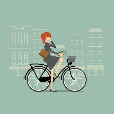 A city scene where a business woman commuter is riding a bike and talking on the phone.