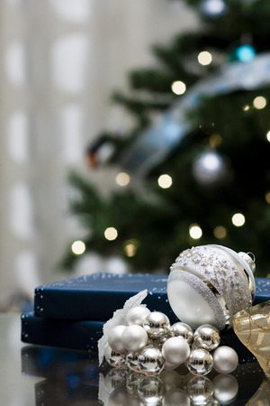 blue giftbox with christmas decorations against christmas tree