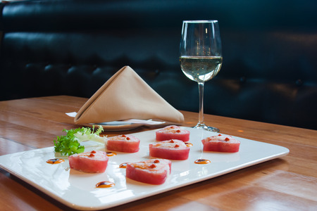 plate of sushi with wine on table Фото со стока