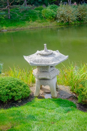 japanese stone lantern by pond Фото со стока