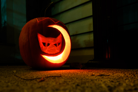 lighted pumpkin carved with cat and moon shape Фото со стока