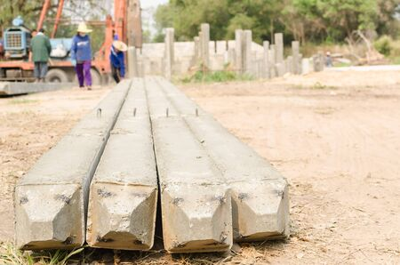 precast: bottom view of precast concrete piles on blurry construction site  background