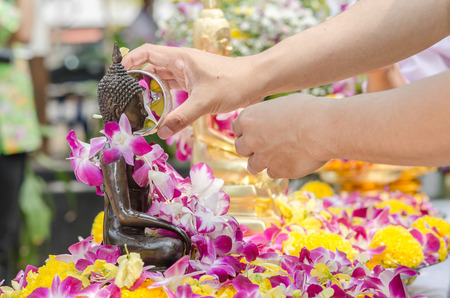 signify: THAILAND - APRIL 09: Thai people celebrate Songkran Festival - the traditional New Years Day from April 13 to 15, by pouring water over Buddha statue to signify cleansing for the new year on April 09, 2015 in Khonkaen, Thailand. Stock Photo
