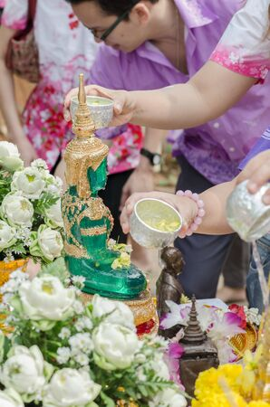 signify: THAILAND - APRIL 09: Thai people celebrate Songkran Festival - the traditional New Years Day from April 13 to 15, by pouring water over Buddha statue to signify cleansing for the new year on April 09, 2015 in Khonkaen, Thailand. Editorial