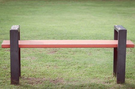 Metallic park bench with grass in the background,vintage style.