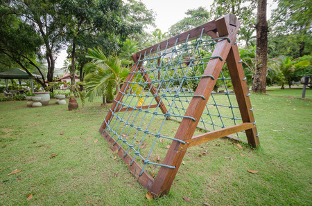 climbing frames: two-sides of climbing net with wooden frame for childrens at the playground. Stock Photo