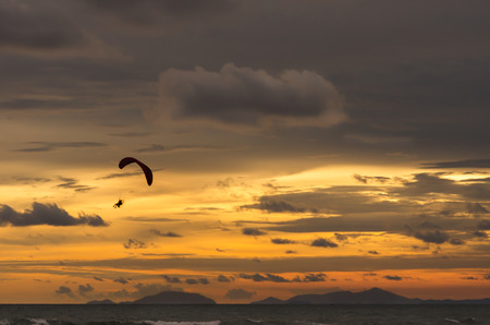 outdoor sport - Silhouette of flying paramotor at sunset on the coast of Jao Lao beach,Jantaburi,Thailand.