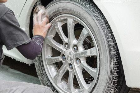 Car washing.A man scrubbing wheels using sponge at car wash station.