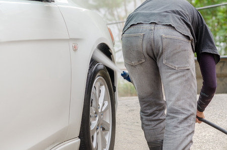 soaping: Car washing.A man cleaning wheels using high pressure water jet at car wash station. Stock Photo