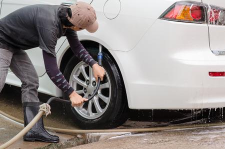 Car washing.A man cleaning wheels using high pressure water jet at car wash station. Stock Photo
