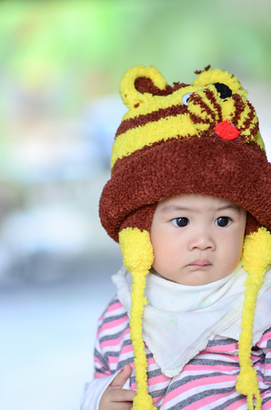 colorful portrait of cute baby boy dressed in lion custume,looking for something on blurry background.