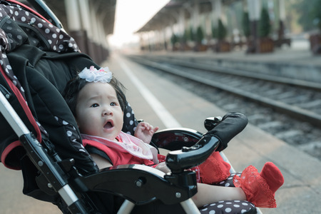 Adorable asian baby girl sitting in stroller on a walk in railway station.
