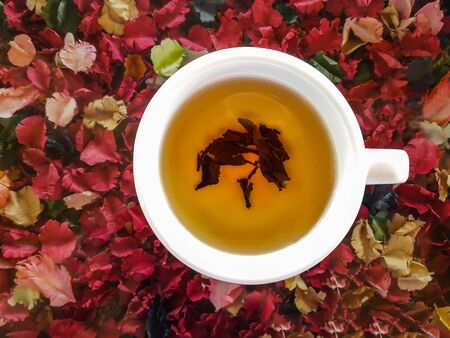 Top view of a cup of hot tea on colorful artificial flowers background. Standard-Bild