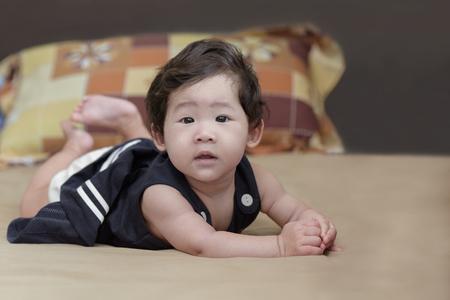 Portrait of adorable asian baby girl lying on bed. Standard-Bild