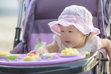 Little asian baby girl sitting and playing in stroller on a walk. Close-up.
