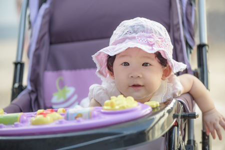 Outdoor portrait of sweet little asian baby girl sitting in stroller and looking her mother during a walk. Close-up.