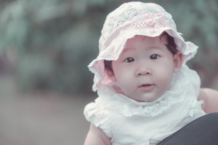 Portrait of sweet little asian baby girl wearing lace apparel in vintage style. Standard-Bild
