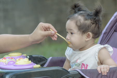 Mother feeding asian baby girl with porridge.