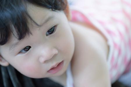 Headshot of cute asian baby girl in pink.