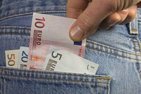 pulling money: Money pulling out of pocket Stock Photo