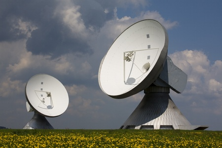 Satellite dishes surrounded by blooming dandelion field in Raisting