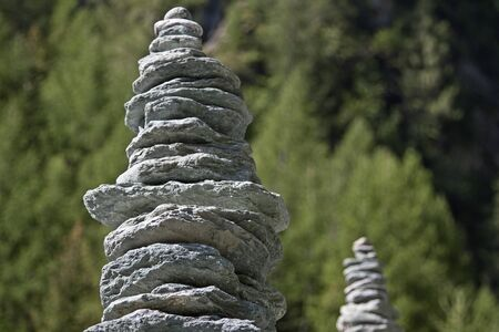 hillwalking: two stone  men shot in front of forest blurred backgroun