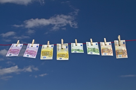 Banknotes fluttering on a clothesline against a green grass in the wind