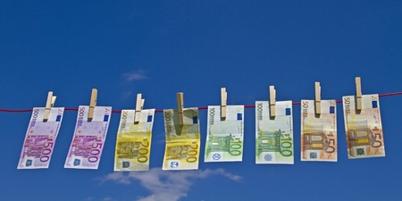 Banknotes fluttering on a clothesline against a blue sky in the wind Stock Photo