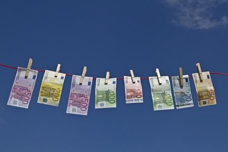 Banknoty fruwające na clothesline na tle błękitnego nieba na wietrze