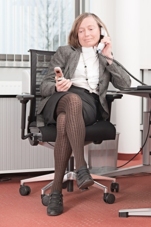 Stressed businesswoman in two telephone calls photo