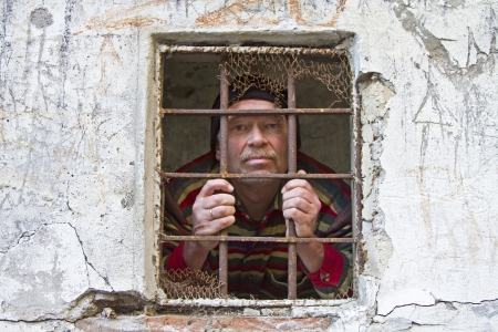 locked up: Man looking through a prison window