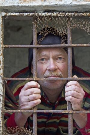 Man looking through a prison window photo