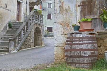 old container: Wooden barrel in front of an old dilapidated house in Croatia