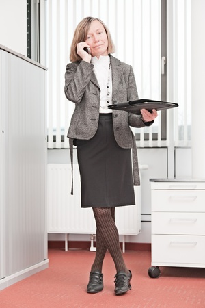 important phone call: Business woman standing takes an important phone call