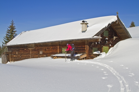 mountain hut: Ski tourers before idyllic hut in Upper Bavaria Stock Photo