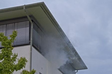 Une fumée qui couve passant d'un immeuble de bureaux Banque d'images - 15875827