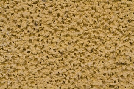 plastered: Coarse yellow plastered wall suitable as background