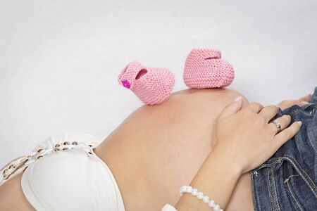 baby bump: Baby bump of a reclining woman with pink baby shoes Stock Photo