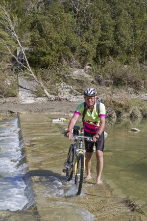 orcia: Man across the river Orcia by bicycle