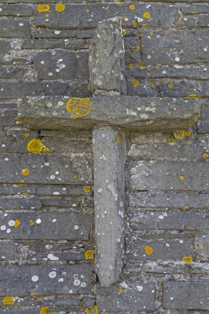 bleak: Stone cross on a stone wall with lichen